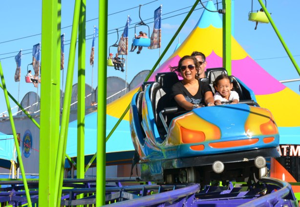 a mother and daughter enjoying a ride, like a roller coaster, as it comes around a corner.