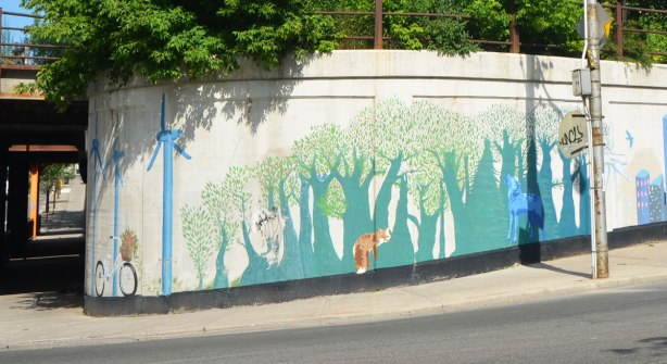mural on a curved concrete wall, beside an intersection, showing windmills with bike parked in front, and a forest with some animals in it, fox and wolf