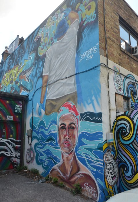 mural on the side of a building, a woman's head and shoulders.  She's in the water and wearing a bathing cap.  Above her is a painting of a man spray painting on a wall.