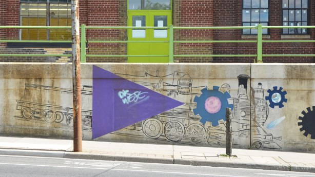 mural on a concrete wall beside a sidewalk, just before the road goes under an underpass - large purple triangel, drawing of a locomotive and a couple of gears