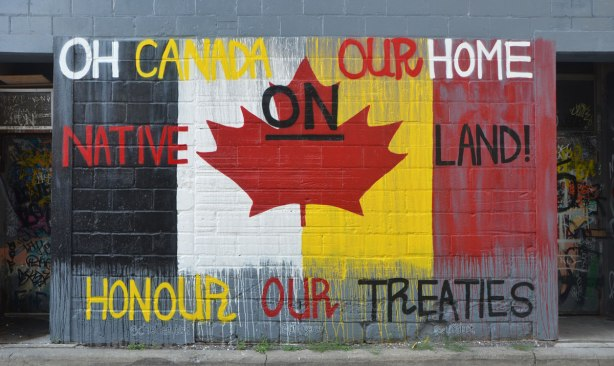 street art on a wall in an alley, Canadian flag with background colours changed to Native flag colours, and words that say Oh Canada Our Home On Native Land. Honour our treaties.