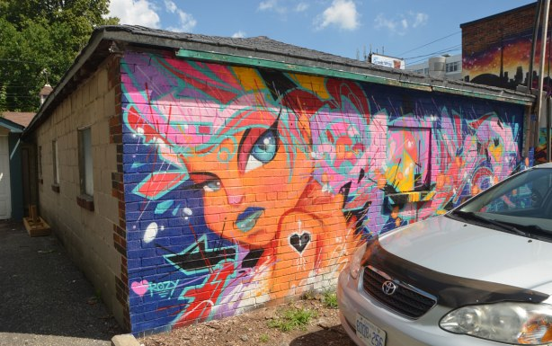 mural on the side of a garage by cruz 1 art, a young girl in orange with many colours abstractions around her