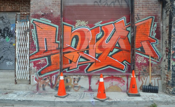 a large orange text graffiti across a large door and on the wall on both sides, all in orange, with three orange traffic cones in front of it.