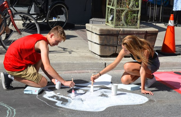 a young man and a young woman painting on the street, painting part of a mural on a street in Kensington market area