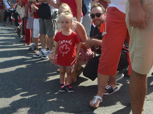 a mother and father are squatting down beside his young daughter who is standing beside a street waiting for a parade to start, amongst other people, little girl is wearing a red Canada T-shirt.