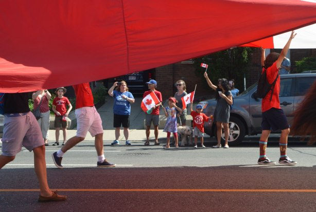 looking under a giant Canadian flag being held up by people, looking across to the other side of the street where some families are watching a parade, and waving Canadian flags.