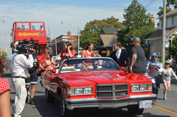 Penny Olesiak and Michelle Williams, two Canadian swimmers who won medals in swimming in the 2016 olympics, ride in the back of a red convertible, a TV camera is on one side of the car and a man interviewing Michelle is on the other side of the car. The car is moving in a parade.
