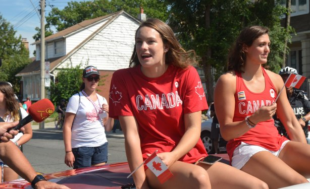 Penny Olesiak and Michelle WIlliams riding in the back of a red convertible in a parade