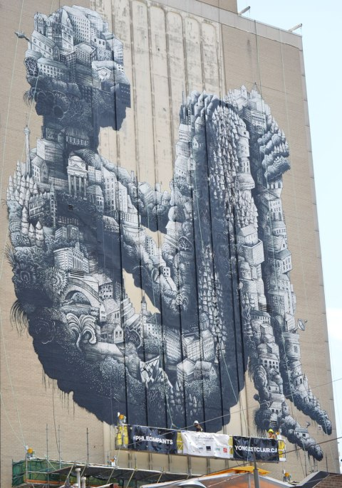 large black and white mural by phlegm of a seated person with their knees bent up, made of tiny houses and buildings and other structures