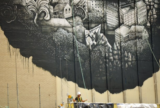 the bottom part of a mural, man in scaffolding is still working on it, black on white, pictures of buildings.