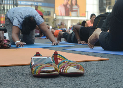 close up of a phone tucked inside a sandal, beside an orange yoga mat. People around are doing yoga outdoors,