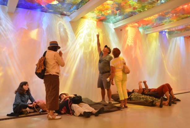 people lying on the floor looking a ceiling that is made of different coloured glass pieces, back lit, also some people standing and pointing at different pieces