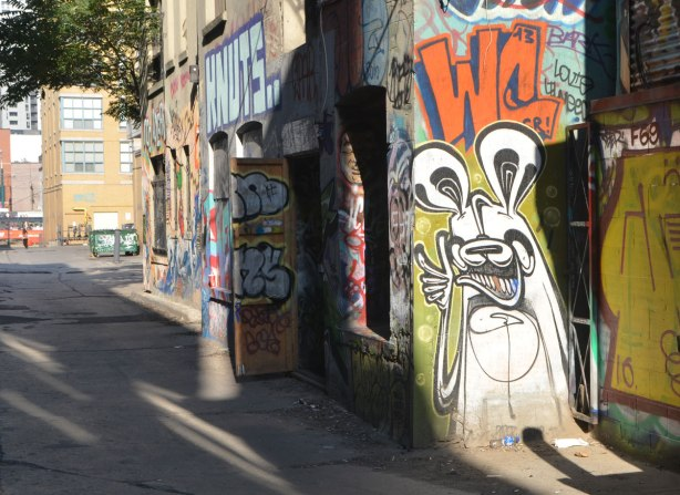 a poser bunny painted on the side of a building, spotlighted by the afternoon sun, the wall behind him is in shadow