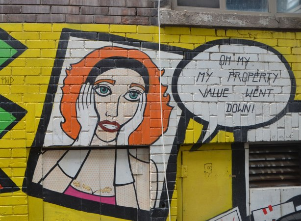 "street art, picture of woman with orange hair, wearing white gloves, hands on sides of head, words saying ""On no, my property value went down"""