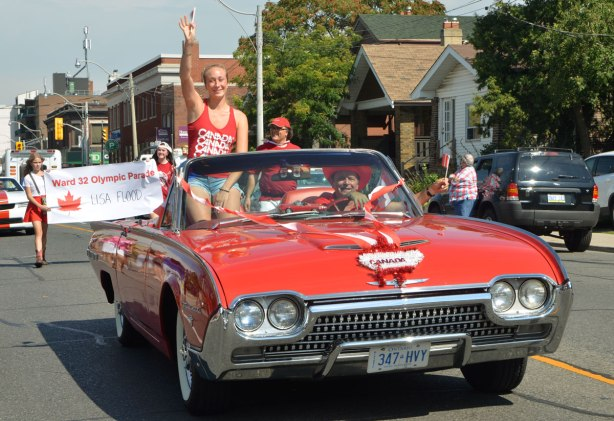 A woman Canadian athlete, Rose Cossar, rides in a red convertible in a parade. She is holding up a small Canadian flag.