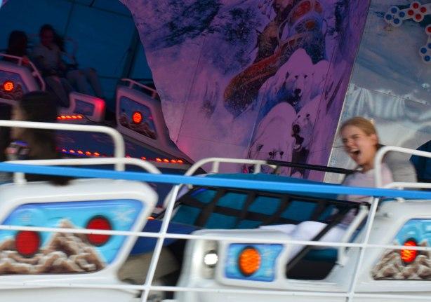 a young woman is screaming as a ride takes her around in circles, she is slightly blurry because of the speed of the ride