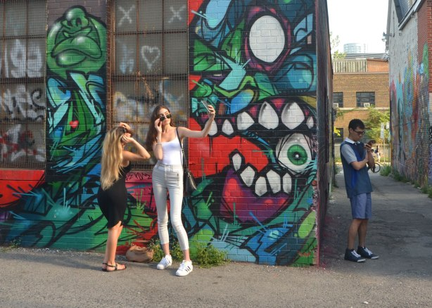 two young women pose in front of a colourful mural in an alley, while around the corner of the building a young man is looking at his phone,