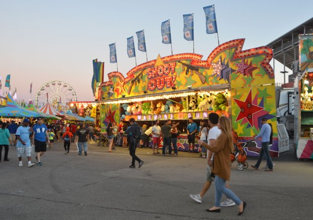 midway game, shoot out, early evening, lights on, people walking in front, ferris wheel in the distance.