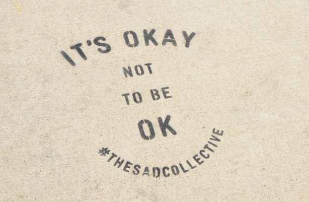 words stenciled onto the sidewalk in black, that say It's Okay not to be OK #thesadcollective