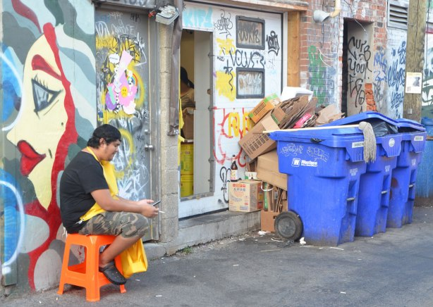 a man is sitting on a small orange plastic stool in an alley. He has a yellow apron on. He has a cell phone and a cigarette in his hands.