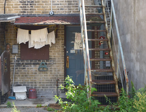 in an alley, back of a store, old rusty metal stairs to the upper storey, small awning over the backdoor, laundry hanging by the door, weeds growing in front of the bottom of the stairs.