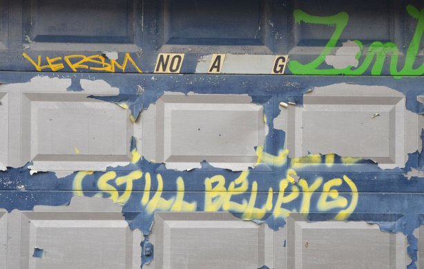 a metal garage door once painted blue, the blue is peeling. Stickers that said no parking have fallen away so there's only NO A G left. Written in yellow spray paint is Still believe.