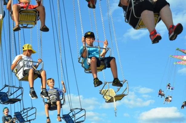 lots of people in swings suspended by chains, about to twirl around at the CNE