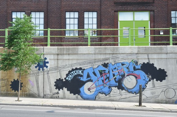 mural on a concrete wall beside a sidewalk, just before the road goes under an underpass, gears, plus a stylized industrial machine in black and blue