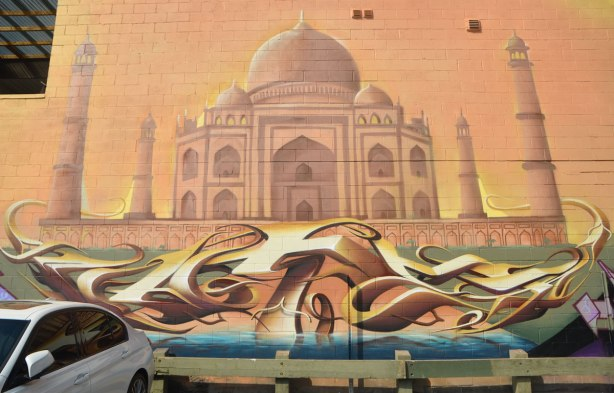 An image of the Taj Mahal in a mural in warm muted orange and brown tones, with a graffiti writing signature underneath it. On a wall in a parking lot.