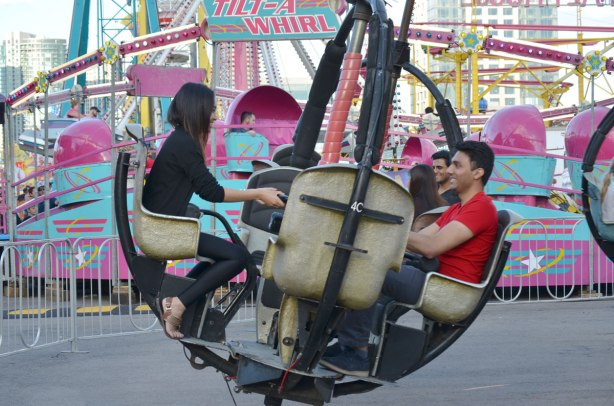 a couple ride on a midway ride at the Canadian Exhibition, behind them is the blue and pink tilt-a-whirl ride