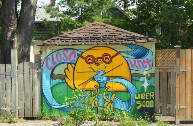 "an uber 5000 art piece on a garage door, yellow uber birdie is knitting something with blue wool. the words say ""close knit"""