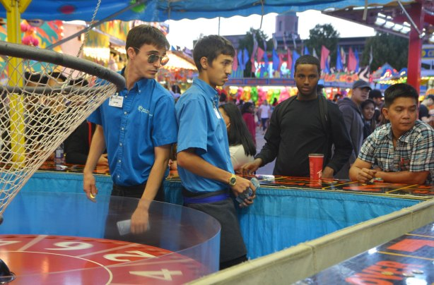 two young men in blue shirts working at one of the midway gambling games, with another man standing behind the counter