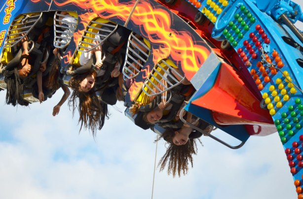 young women upside down on the Fire Ball midway ride, their long hair hanging down.