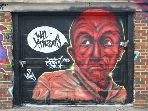 street art mural on a garage door, head and shoulders of a man in red tones,