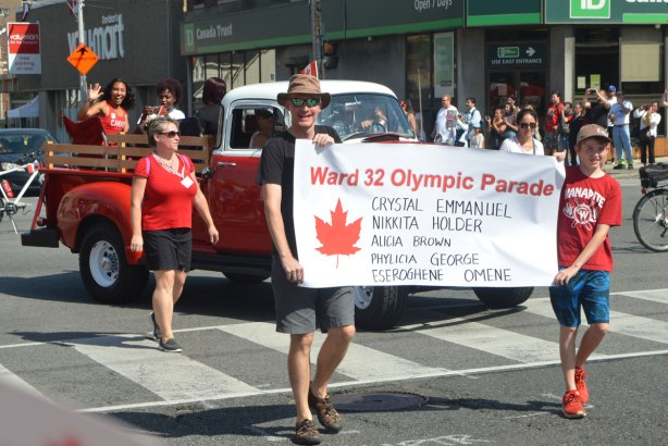 a man and a boy hold a banner in a parade, banner says ward 32 olympic parade. And then it lists the athletes that are riding in the old red and white pick-up truck behind the banner, Crystal Emmanuel, Alicia Brown, Nikkita Holder, Philicia George and Eseroghene Omene