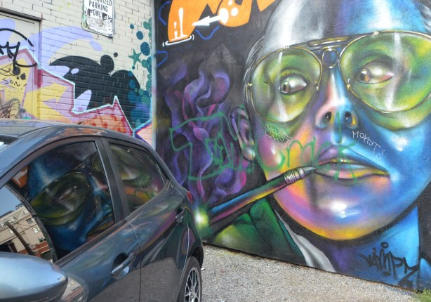 mural of a large face with paint brush by the mouth, wearing glasses, mural seems to be looking at a car that is parked in front of it, with reflections of the mural in the car window
