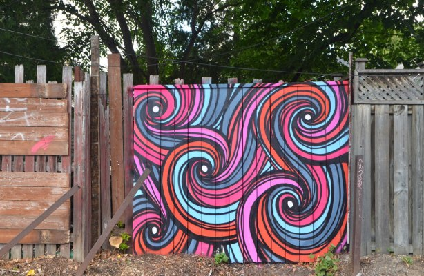 a section of wooden fence covered with street art in pink and orange and turquoise and purple striped swirls