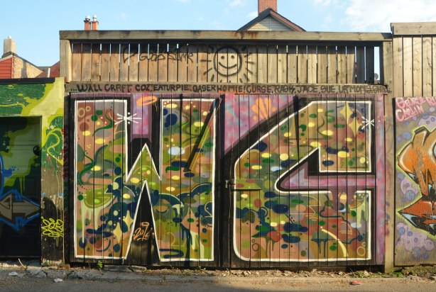 wood double garage door, center opening, with a large street art W and C painted on it.