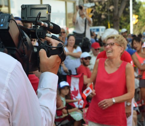 Camera man with TV camera is in focus, with his back to the camera, Kathleen Wynne is in the background and is slightly out of focus.
