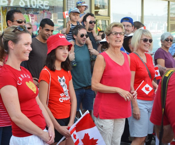 Ontario premier Kathleen Wynne stands amongst some people on a sidewalk who are waiting for a parade to start