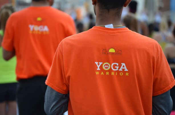 Two men, one in focus in the foreground and one fuzzy in the background. they are both wearing orange t-shirts that say yoga warrior on the back.