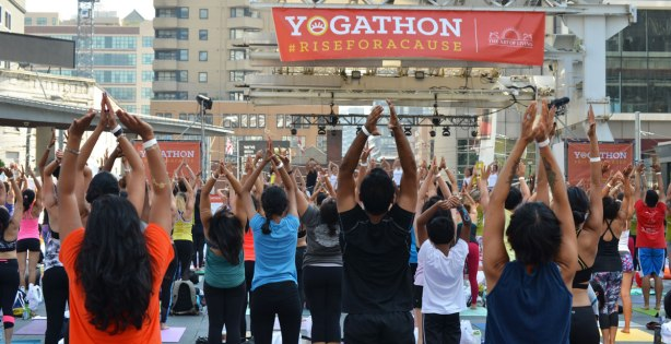 A banner that says Yogathon rise for a cause hangs over a crowd who are standing with their arms in the air as part of the activity
