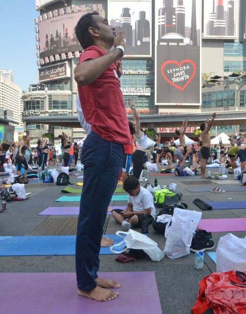 a man in red shirt and blue pants is standing tall, others around him also standing in yoga position, a boy is sitting on the ground with his legs crossed and looking at something in his lap