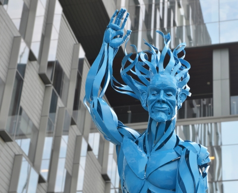 top part of a blue metal sculpture of a man, showing his head, with long hair flowing out behind, one arm raised. The glass windows of a building are behind him, outdoors,