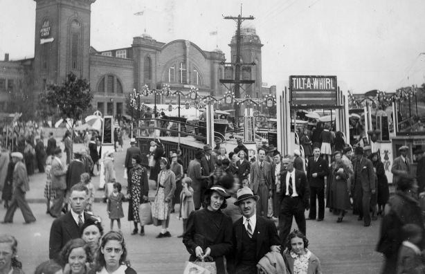 an old black and white photo of the midway at the CNE taken in 1937, lots of people in period clothes, an olf tilt-a-whirl ride also in the picture.