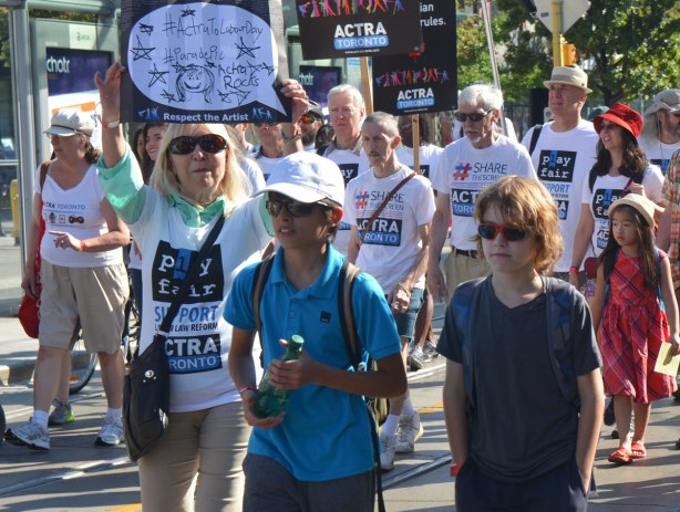 members of the actra union walking in a parade, a woman looking at the camera and holding a sign above her head, two boys walking beside her. One in sunglasses and with hands in his pockets.
