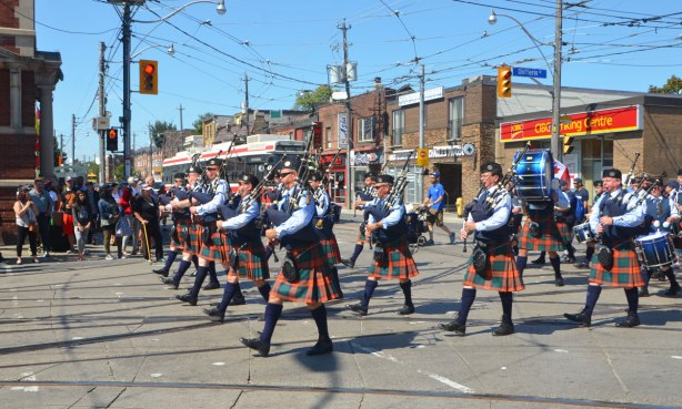 pipe band, bagpipes and drums, marches through the intersection of King and Dufferin in the annual Labour Day parade, people watching on the sidewalks, a TTC streetcar waiting for the parade to pass