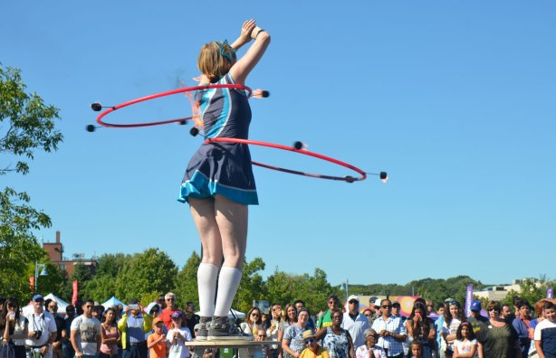 woman standing on a stool with two hula hoops around her middle, both of which have 5 or 6 spots that are on fire, in front of a crowd of people sitting on the grass