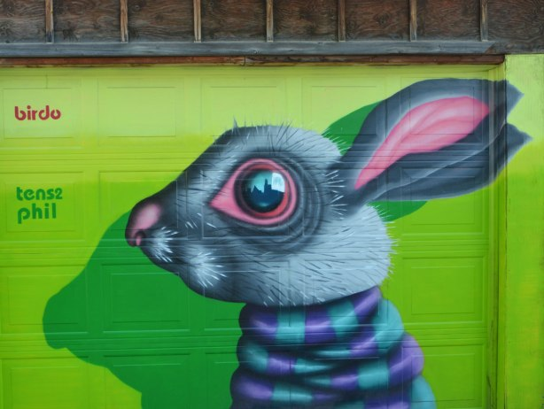 birdo street art of a rabbit head on a bright green garage door, grey head, pink inside of the long ears, purple and turquoise striped neck.