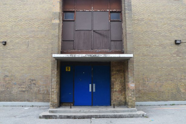 blue double doors in a drab brown brick building, with brown metal inserts covering what was once a large window above the door. Two small windows remain.